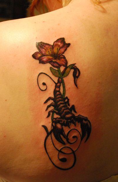 modele tatouage scorpion feminin avec fleur et arabesque sur omoplate haut du dos gauche