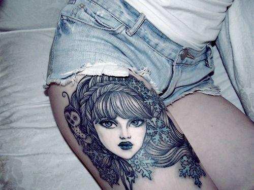 tatouage femme cuisse tete de personnage
