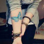 Tatouage papillon couleur bleu avant bras interieur