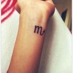 tatouage signe astro m et fleche du scorpion fille interieur poignet