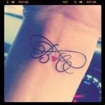 modele tatouage poignet initiales en calligraphie et coeur rouge