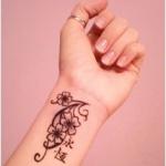 tatouage poignet femme fleurs arabesques et ideogrammes japonais