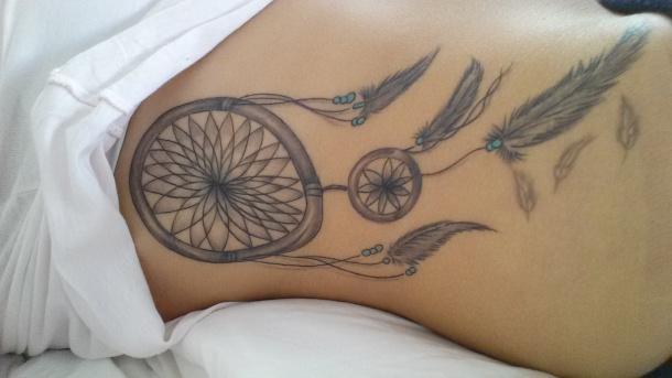 tatouage femme attrape reve hanches avec plumes