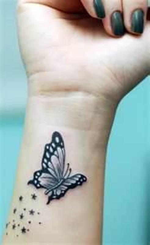 papillon tatoue sur femme interieur poignet avec des etoiles