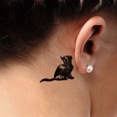 Tatouage petti chatnoir assis derriere oreille
