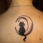 Tatouage sous nuque femme avec chat assis de dos sur un croissant de lune