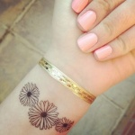 Tatouage femme discret 3 fleurs poignet
