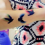 3 oiseaux tatoues sur avant bras avec lueur verte bleu et rose