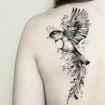 Beau tatouage oiseau femme dos avec fleurs et ailes deployees