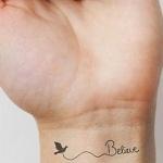 Tatouage femme oiseau relie a un mot believe interieur poignet