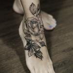 Tatouage grande rose noire et ses feuilles pied et bas de jambe fille