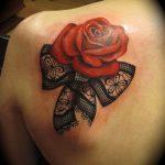 Tatouage dos omoplate avec rose rouge et noeud en dentelle
