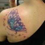Etoiles scintillantes et papillon tatoues sur epaule cote dos