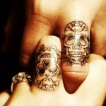 photo tattoo feminin doigt tete de mort recouvrant une phalange