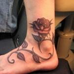 tatouage femme cheville rose eclose tige et feuilles