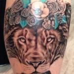 beau tatouage femme lion cuisse avec couronne de fleurs roses et feuilles bleues