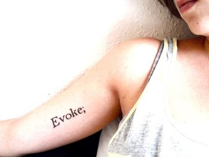 photo tattoo feminin evoke point virgule sur le haut du bras