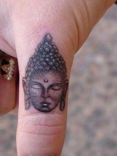 photo tattoo feminin bouddhiste sur doigt