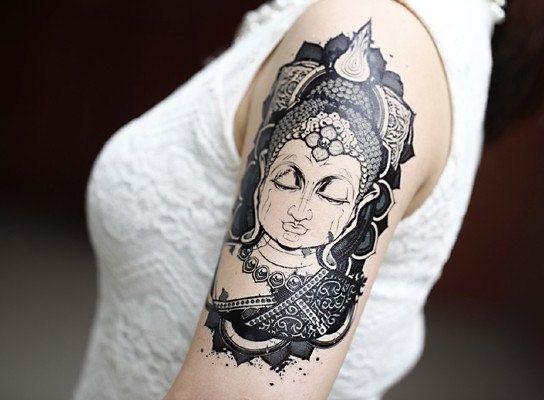 tatouage symboles bouddhistes fille tete de buddha haut du bras