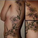 tatouage femme grande branche arbre avec belles fleurs roses dos et flanc