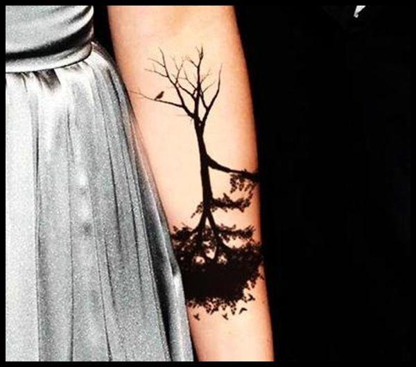 tatouage symboles arbre a l envers bras feuillage et racines en haut