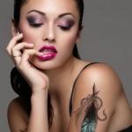 beau tatouage femme plume noire et bleu haut du bras