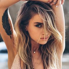 beau tatouage plume noire fille haut du bras interieur