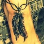 modele tatouage 2 belles plumes noires en pendentif sur pied avec bracelet cheville