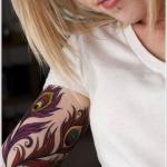 tatouage femme 2 plumes de paon haut du bras