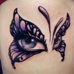 papillon avec regard dans les ailes tatouage femme