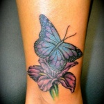 photo tattoo feminin papillon sur fleur cheville mollet