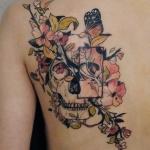 tatouage papillon femme avec fleurs et tete de mort