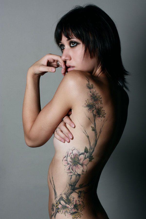idee tattoo dos et flanc femme fleurs et morceaux d arbres