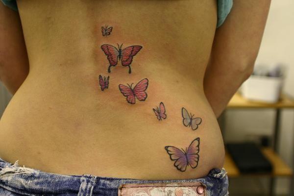 tatouage symboles papillon bas du dos fille cote droit - tatouage femme