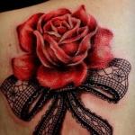 modele tatouage rose rouge eclose en relief avec noeud dentelle sur omoplate