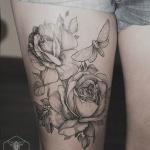 tatouage rose noir et blanc femme avec papillon suir cuisse
