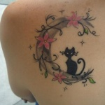 Tatouage femme chat avec fleurs et arabesques