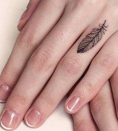 Tatouage femme discret dessus du doigt belle plume