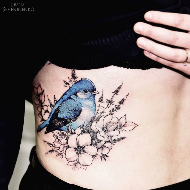 Tatouage oiseau bleu avec fleurs flanc femme