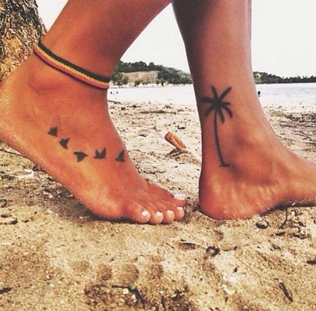Tatouage symboles oiseaux pied et arbre palmier sur l autre
