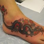 Idee tattoo dragon et fleur de cerisier rouge pied femme