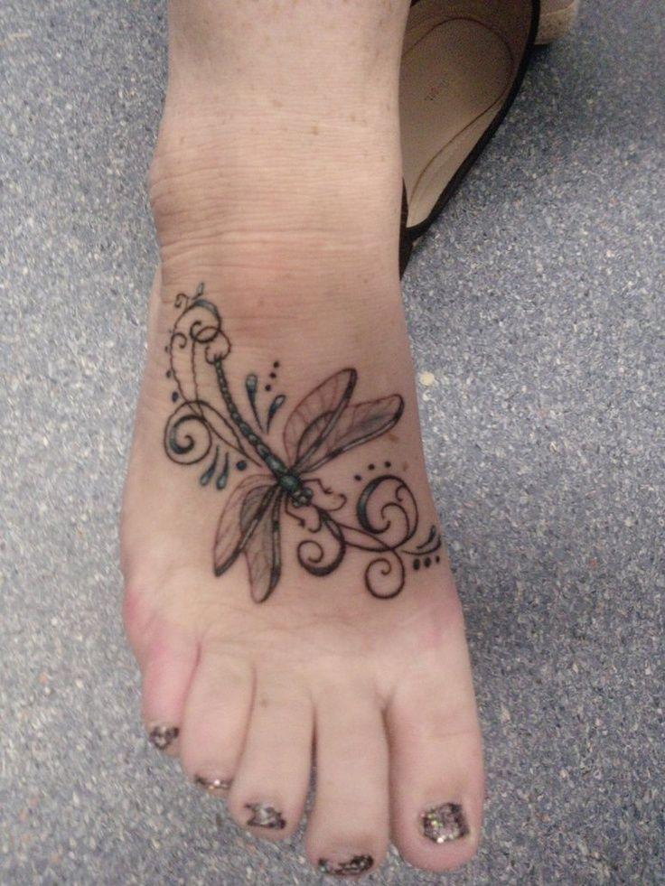 Tatouage femme dessus de pied libellule et arabesque