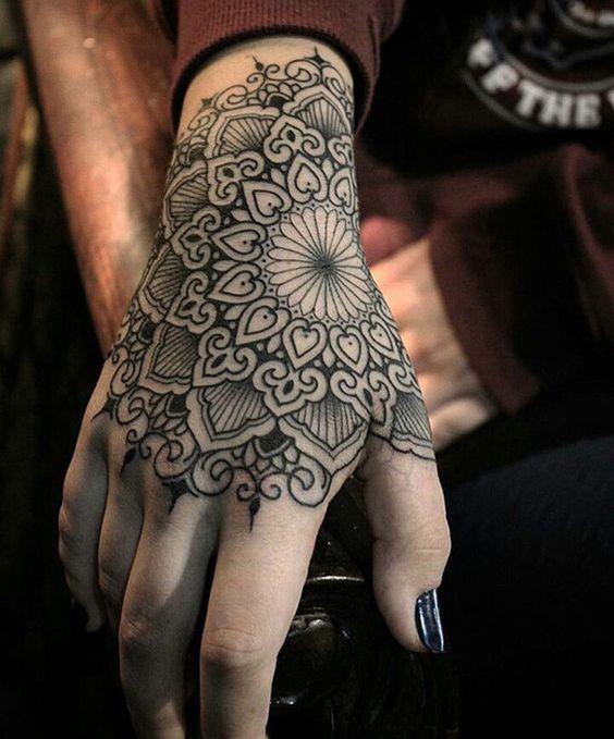 Tatouage symboles mandala fille recouvrant la main