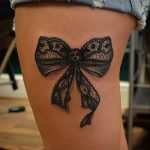 Photo tattoo feminin noeud en dentelle sur cuisse