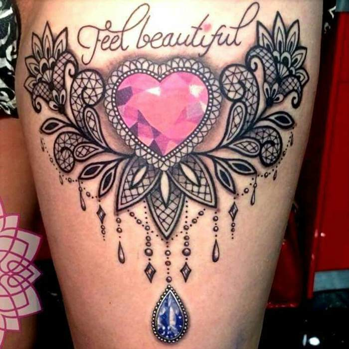 Tatouage femme coeur entoure de dentelle avec phrase sur cuisse