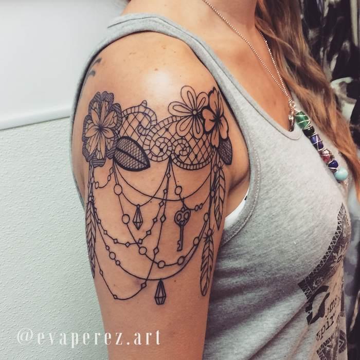 Tatouage haut de bras femme dentelle fleur plume et bijoux