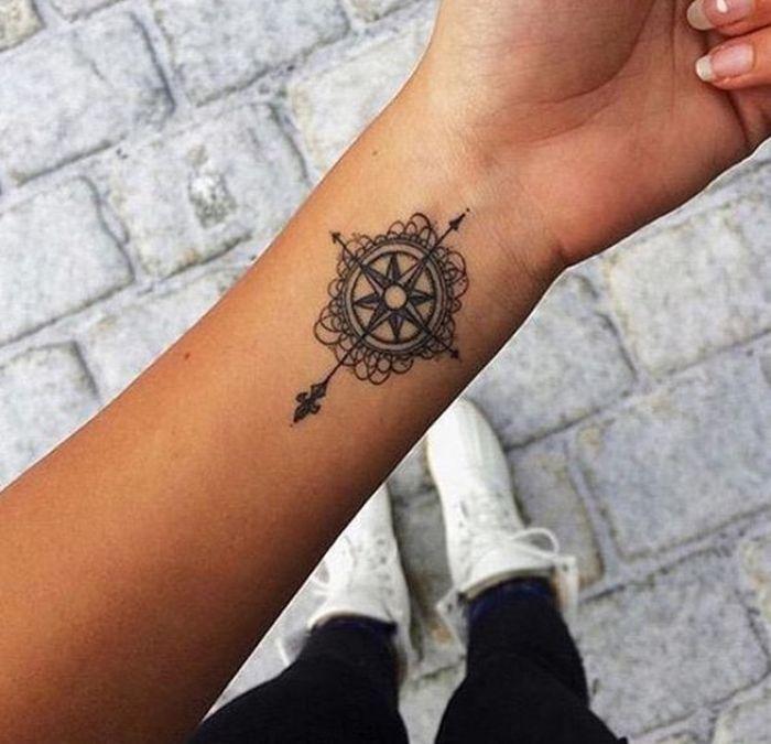 Joli modele tatouage rose des vents avec fleur de lys et fleche interieur poignet