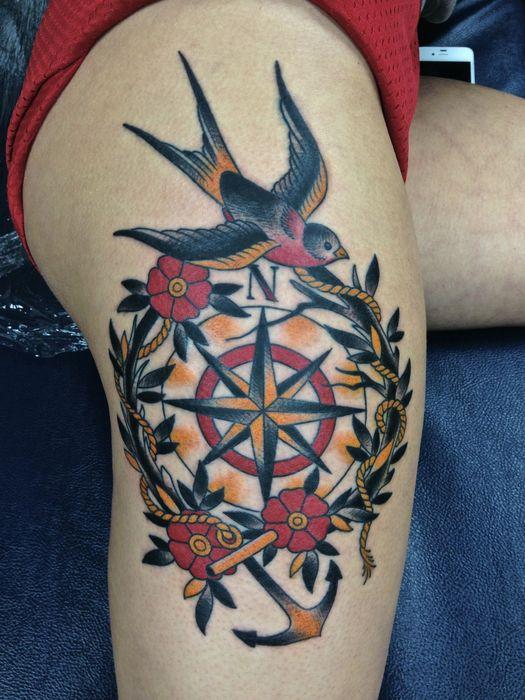 Modele tatouage oldschool hirondelle et ancre sur boussole entoure de fleurs et feuillage