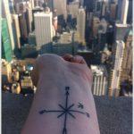 Tatouage femme boussole simplifie avec croix au centre