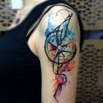 Tatouage haut du bras style aquarelle boussole fille